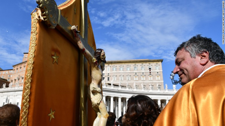 A pilgrim holding a crucifix attends the Pope's Angelus Sunday prayer in St. Peter's square.