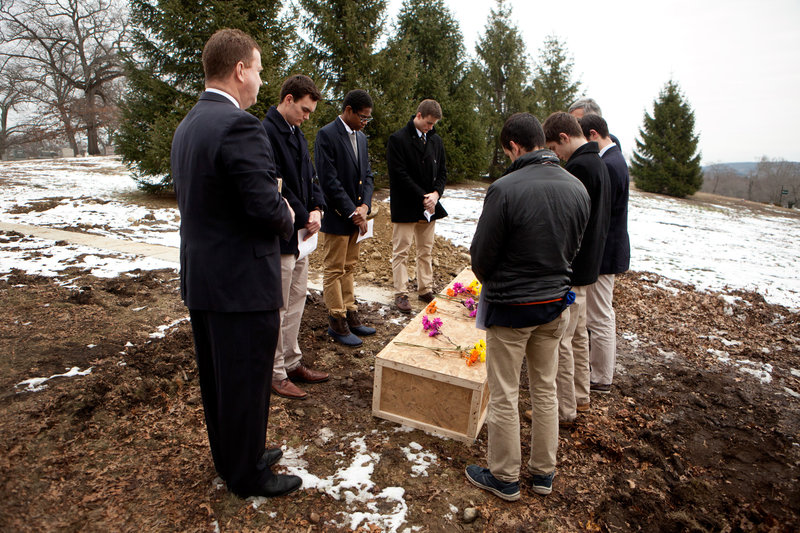 From left to right, funeral director Rob Lawler; Roxbury Latin students Emmett Dalton, Noah Piou and Chris Rota; Roxbury Latin assistant headmaster Mike Pojman, and Roxbury Latin students Brendan McInerney, Liam McDonough and Esteban Enrique conduct a graveside prayer service for Nicholas Miller on Friday at the Fairview Cemetery. |Kayana Szymczak for NPR|[/caption]